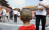 OLYGY103 - A little boy with the Olympic rings shaved into the back of his head visits the...