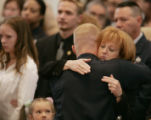 "Kelly Young, widow of Denver Police Detective, Donald ""Donnie"" Young, right, gets a hug..."