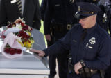 Denver Police  Detective John Bishop touches Detective Donald Young's casket at the end of a...