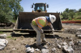 Ricardo Caldera (cq) cleans up an old train bridge that was demolished in preparation for a new...