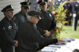 Denver Police Detective Jeff Baran (cq) places his gloves on the casket of his former partner and...