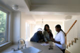 (PG480) Realtor Kathy Casey (center) talks with Ricardo Collins and his daughter Angela Boyd about...