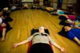 Theresa Lee (cq) places a bean bag over her eyes as a way to deeply relax the body, shutting out...