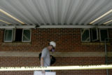 Disaster Restoration, Inc. structure technician Sean Dunn boards up windows of a house at 7120...