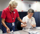 Election workers Gretchen Howard, left, and Karen Hoffman preprocess mail-in ballots at Centennial...