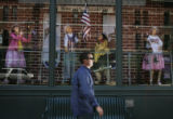 A man walks by a window display at the Oxford Hotel in Downtown Denver, depicting a scene of...