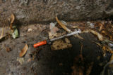 1831  A discarded syringe lies in a corner of the Greek Amphitheater in Civic Center Park in...