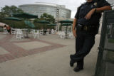 280  A Denver Police officer stands watch as diners sit under umbrellas and have lunch during the...