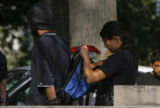 456  A Denver Police officer searches a man's backpack before he was taken into custody on drug...