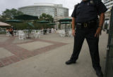 278  A Denver Police officer stands watch as diners sit under umbrellas and have lunch during the...