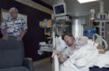 Eric Balzer (LEFT, and standing) listens as his son Ryan,27, (RIGHT and in bed) discusses his...