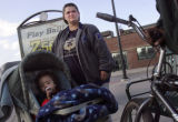 Shannon Thill (cq), 27, waits at a bus stop with her child, Terrell Grimes, 15 months, after going...