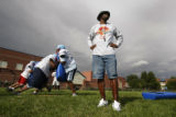 Coach Dwayne Davis keeps an eye on his team as they practice at Manueal HS in Denver, Colo, on,...