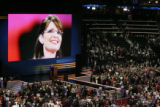 An image of Sarah Palin is shown on the screen behind the stage while speakers take turn talking...