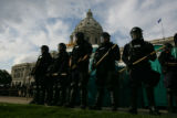 Police in riot gear stand at the ready at the State Capitol in St. Paul on the final day of the...