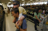 Wyatt Esp, 5 sits on the shoulders of Brian Havermann with mom Abby Havermann (r) of Arvada as...