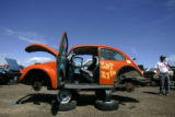 An orange Volkswagon Beetle sits in the lot at the U-Pull-&-Pay, a new self-serve auto parts...