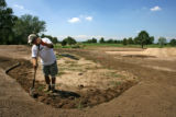 Mike Bowline (cq) works on creating a sand drap on the 4th hole, Monday afternoon, August 18,...