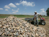 Paco Espinoza (cq) moves rocks to repair the trickle chanel, Monday afternoon, August 18, 2008, at...