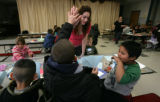 Miguel Hildago,6 (r) laughs as Raphael Moreles, 7 high fives teacher Karina Cardenas  after he...
