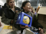 Alberto Romero, 8 picks out gifts as his mother Juanita Romero looks on at The Denver Santa Claus...
