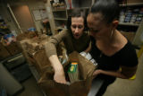 Volunteers, Leeann Gardenswartz and Simone Pickford places food in the bags for clients in the...