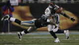 JPM748 Denver Broncos Tatum Bell (21) bobble the ball as he is tackled by Carolina Panthers Thomas...
