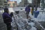 City of Denver employees shovel snow off the sidewalk of the 16th Street Mall as they are shown...