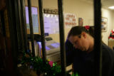 Amy Hauptman (cq) works the front counter near a memorial set up for Tim Minnick at the Grizzly...