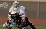 Golden's Nick Robinson (bottom red) gets smashed by Cherry Creek's Dane Mueller (top white) in the...