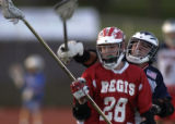 Kent Denver's Matt Kelsic (right #12) tries to knock the ball loose from Regis High School's Chris...