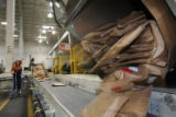 (at left) Mail handler, Monika Ledford (cq) sorts out packages at the U.S. Post Office Bulk Mail...