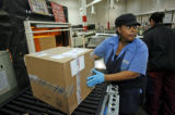 (at left) Mail handler, Regina Jones (cq) and her co-worker, Tamara Paris (cq) sort out packages...