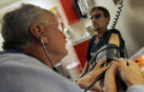 Adavnced Nurse Practitioner Jack Moore (cq), left,  takes the blood pressure of Roy Gregory (cq),...