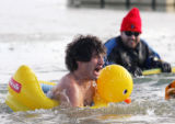(0697) Jesse Gettert wades into the water with an inflatable duckie at the Polar Plunge at the...