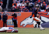 (0193) Jay Cutler hops out of the grasp of Ryan Denney in the second quarter of the Denver Broncos...