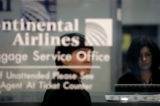 (PG5692) Chris Choi, of New Jersey, checks on a lost bag at the Continental Airline baggage...