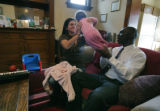 Carl Anderson with his wife Tammy and daughter Kirelle 10 months relax in their apartment Monday...
