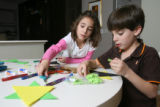 Twins Rebecca, left,  and Casey Zickerman, who are Jewish, make Christmas tree ornaments at their...