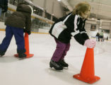 Ainsley Harris 5, right uses a cone for some stability as she learns how to skate at the...