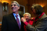 (1032) Newly-elected Colorado Senator Mark Udall smiles as his wife, Maggie Fox, pins his Senate...