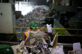 Rosa Maria Lopez (cq) sorts through recycling material at Altogether Recycling at 645 W. 53rd...