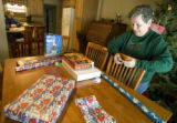 Jim Cruise (left) reads as his mother Lee Monson of Parker, Colorado wraps presents at his home in...