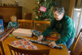 Brandon Monson, age 4, watches his grandmother Lee Monson of Parker, Colorado wraps presents at...