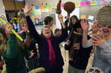 Toni Theisen (cq) ,center, sings a song in French with senior students during French 4 class at...