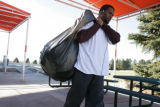 Marlon McCree carries his belonging from his locker to car at Bronco Headquarters in Centennial,...
