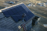 Steve Carroll (cq) of Namaste Solar Electric walks along a roof after installing Sunpower 225 watt...