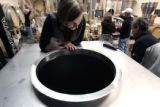 Jackie Thompson, the winemaker at Boulder Creek Winery in Boulder, CO,  looks into a portable tank...