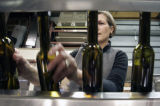 Jackie Thompson, the winemaker at Boulder Creek Winery in Boulder, CO, runs a bottling machine as...