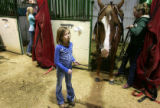 (0496) Payton Neiberger, 8, of Fort Collins, holds the reins, while Kili Crawford saddles her...